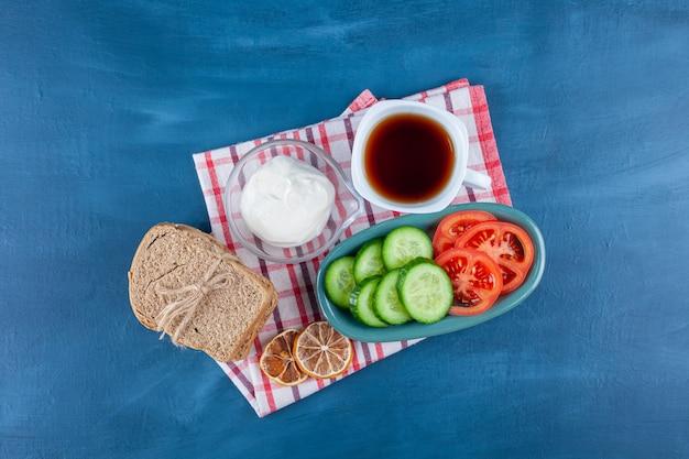 썰어 야채 접시와 파란색 표면에 뜨거운 차 한잔.