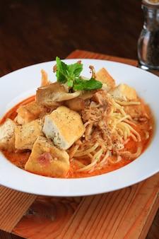 스파게티, 빵 조각 및 채소로 장식 된 수프 접시
