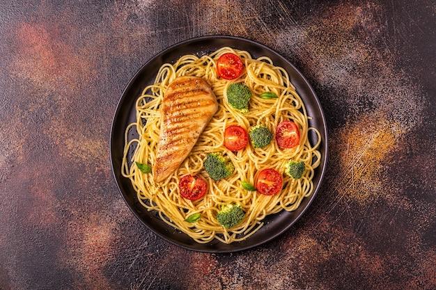 Тарелка спагетти с помидорами, брокколи и курицей