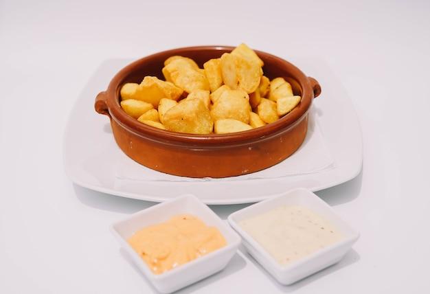 Тарелка испанского пататас бравас с острым соусом