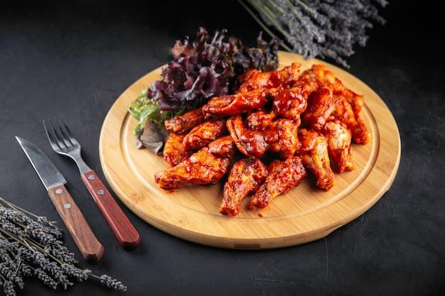Тарелка острых жареных куриных крылышек с салатом