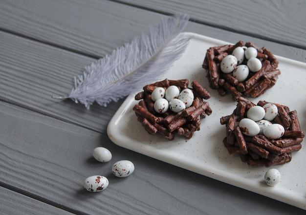 灰色の装飾的な羽を持つ灰色の木製テーブルのイースターエッグで満たされた春のチョコレートの巣のプレート。イースターのお菓子のコンセプトのクローズアップ