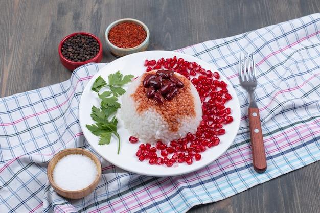 Тарелка вареного риса с зернами граната на скатерти