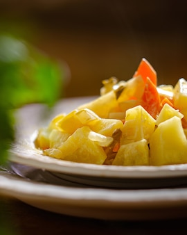 Тарелка тушеного картофеля с морковью на деревянном столе. деревенский стиль, простая легкая еда.