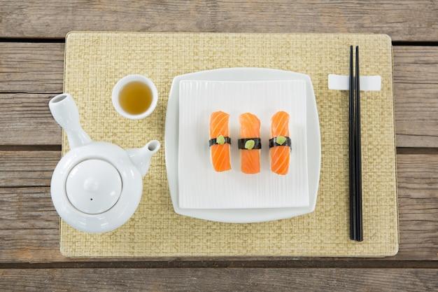 マットの上に置かれた寿司とティーポットのプレート