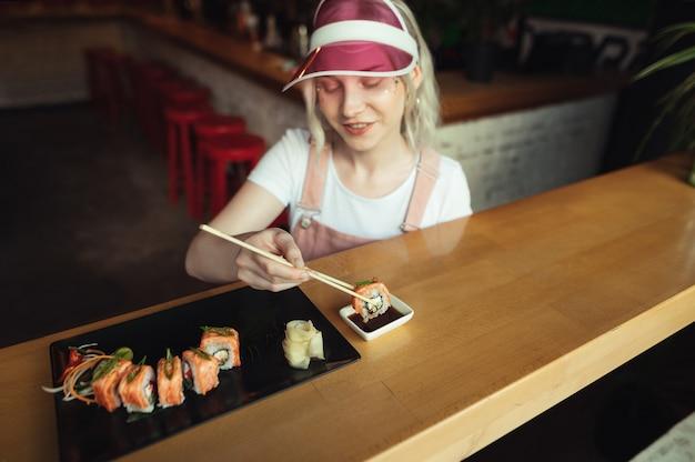 Тарелка суши-роллов в ресторане с женщиной, держащей палочки для еды
