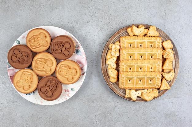 대리석 배경에 누적 된 비스킷 트레이 옆에 타트 쿠키 접시. 고품질 사진