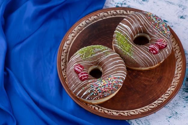 흰색 표면에 뿌리와 맛있는 초콜릿 도넛의 접시.