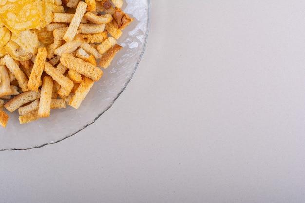 白い背景の上のおいしいクリスピークラッカーとチップスのプレート。高品質の写真