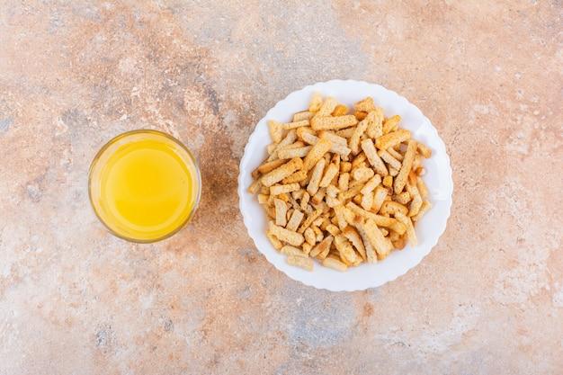 Тарелка вкусных хрустящих крекеров и стакан сока на мраморном фоне. фото высокого качества