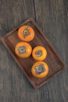 나무 표면에 맛있는 후유 감 과일 접시