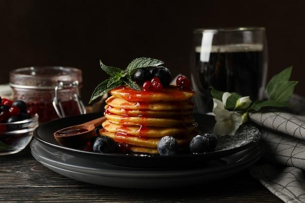Плита вкусных блинчиков с ягодой и порошком на деревянном столе. состав сладкого завтрака