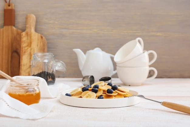テーブルの上に新鮮なブルーベリー、バナナ、蜂蜜とおいしいパンケーキのプレート