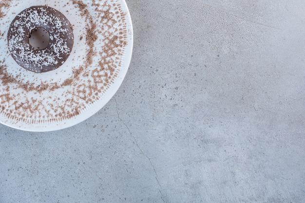 Тарелка вкусного единственного шоколадного пончика на каменном столе.