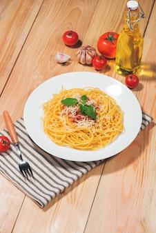Тарелка вкусных спагетти с томатным соусом и мясом на деревянном столе.