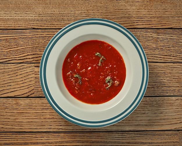 나무 배경에 고기 국물에 두꺼운 토마토 수프 접시