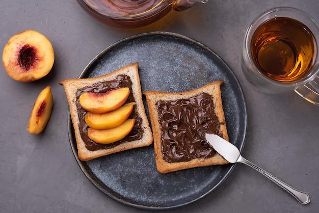 灰色のコンクリートの背景にお茶を入れたプレートに桃のスライスとチョコレートペーストのトーストのプレート。