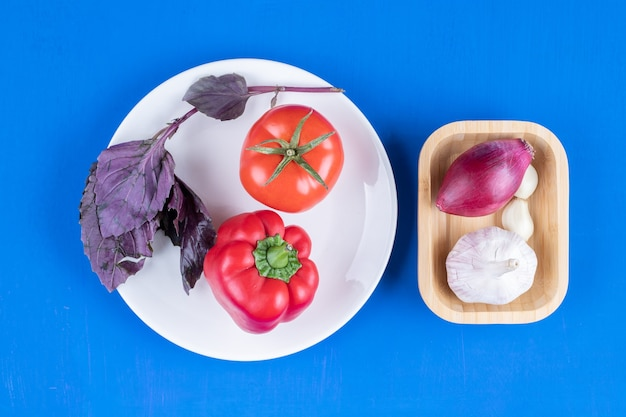 青い表面に玉ねぎとニンニクのボウルとトマトとコショウのプレート
