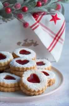 伝統的なクリスマスのlinzerクッキーのプレートは、クリスマスの装飾が施された白いテーブルにいちごジャムでいっぱい