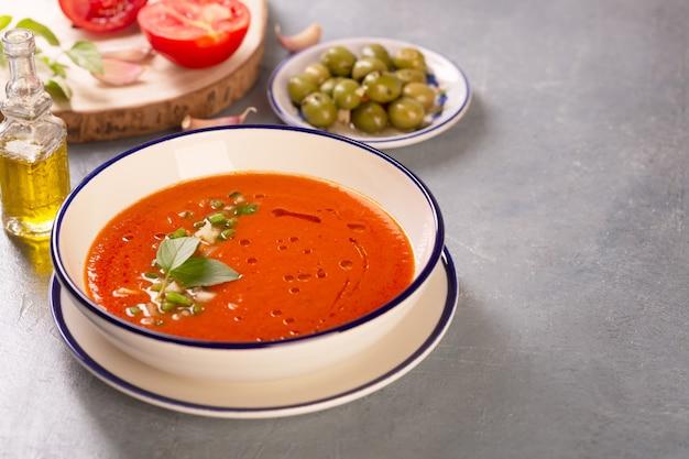 올리브 오일 복사 공간이 있는 토마토, 후추, 마늘로 만든 재료의 배경에 있는 전통적인 스페인 가스파초 접시