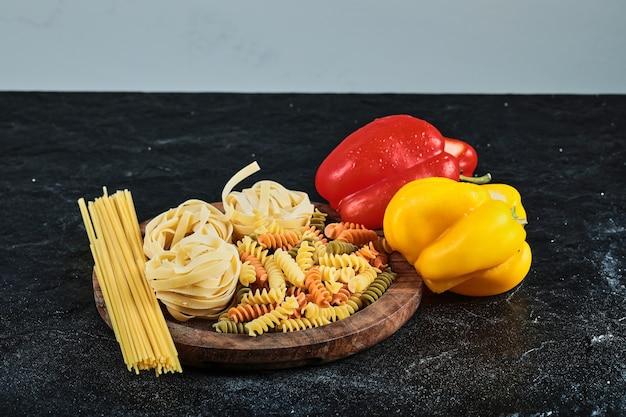 Тарелка сырых различных макаронных изделий и перца на темном столе.