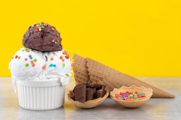 バニラとチョコレートアイスクリームスクープのプレートは、黄色の背景にチョコレートの部分とワッフルコーンを振りかけます。