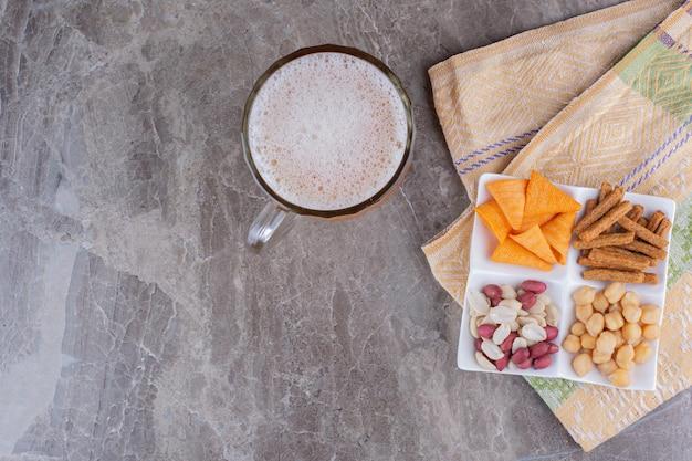 Тарелка разнообразных закусок и пива на мраморной поверхности. фото высокого качества