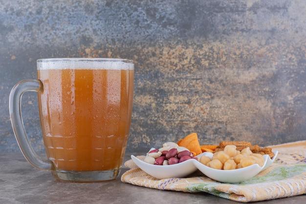 Тарелка разнообразных закусок и пива на мраморном столе. фото высокого качества