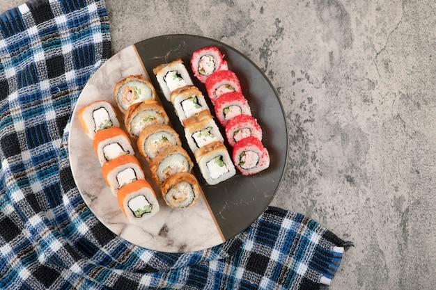 Тарелка различных вкусных суши-роллов на мраморном столе