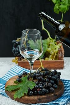 다양 한 포도의 접시와 와인 병 흰색 테이블에 와인 한 잔. 고품질 사진