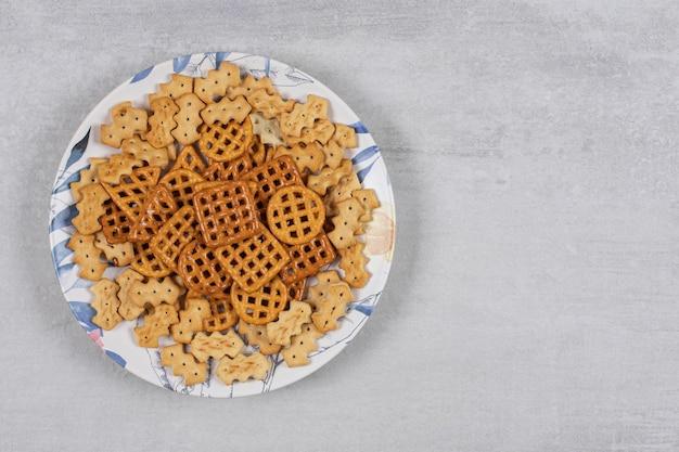 Тарелка различных соленых крекеров на камне.