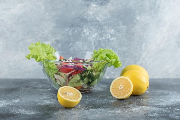 Тарелка овощного салата и лимона. фото высокого качества