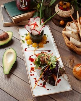 Тарелка овощного салата с листьями салата, темным базиликом, авокадо, желтыми помидорами черри