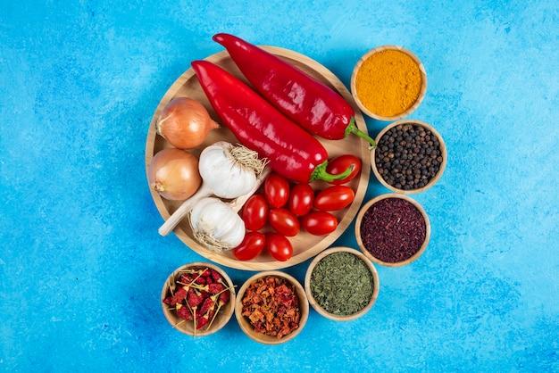 야채와 향신료 파란색 배경에 접시입니다.