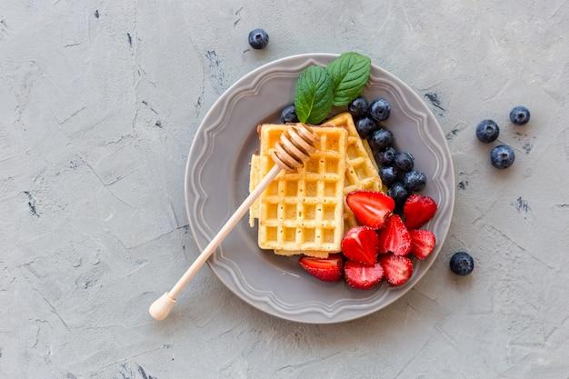회색 돌 표면에 꿀과 신선한 딸기로 장식 된 와플 접시. 음식 개념. 평면도.