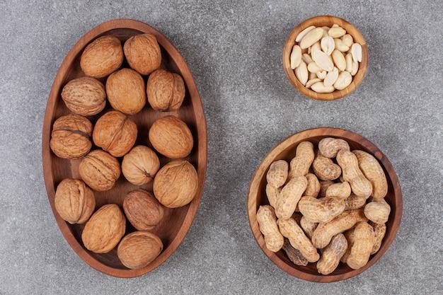 Тарелка грецких орехов, арахиса и кешью на мраморной поверхности