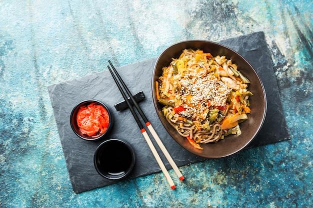 푸른 돌 위에 고기와 야채를 곁들인 냄비 또는 볶음 국수 접시