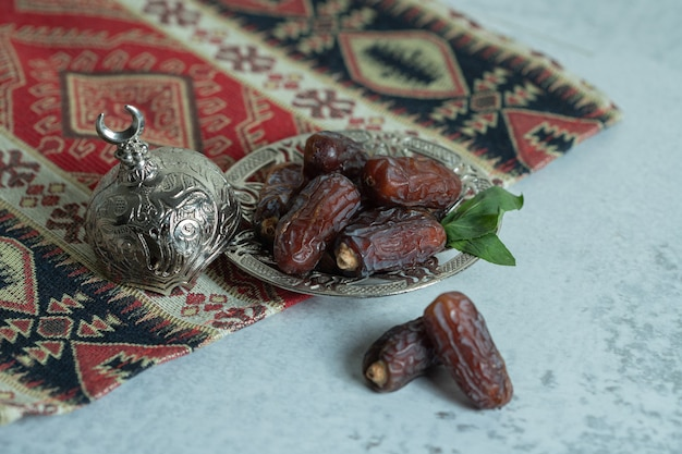 Plate of organic dates on stone surface.