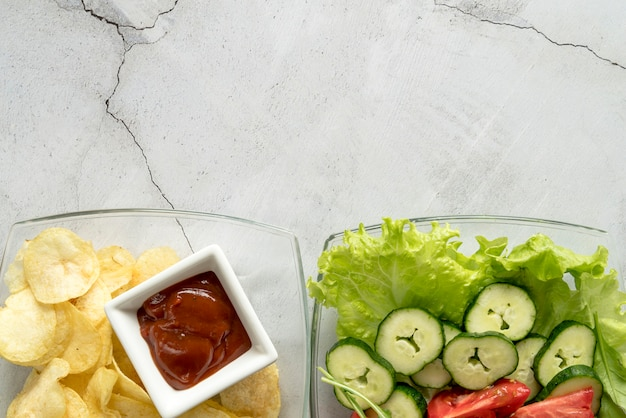 Plate of organic vegetable salad and potato chips with tomato sauce over concrete backdrop