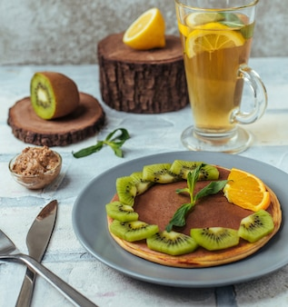 Plate of pancake with spreaded chocolate and kiwi, ornage slices