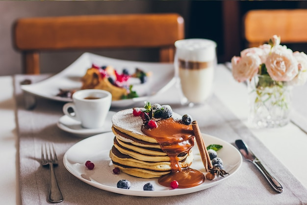 Plate of pancakes with caramel with cranberries and blueberries