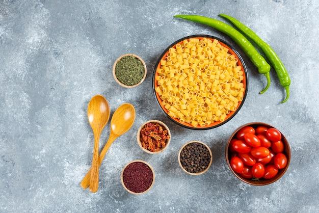 Piatto di pasta, ciotola di pomodori e spezie su sfondo marmo.