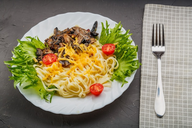 A plate of pasta with cheese and mushrooms decorated with herbs on a gray background next to a fork and a napkin. copy space. horizontal photo