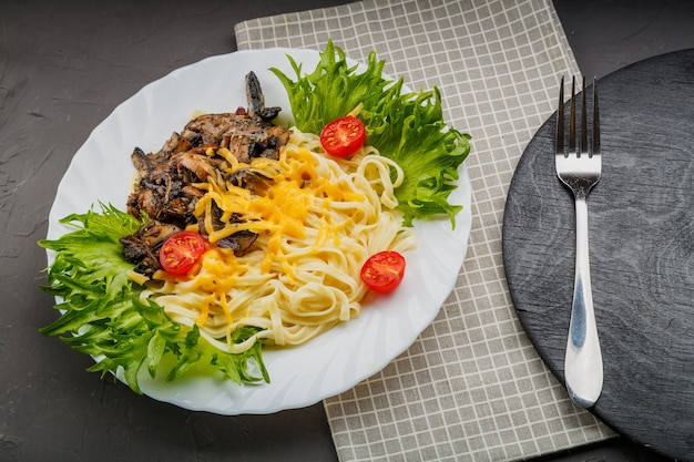 A plate of pasta with cheese and mushrooms decorated with herbs on a gray background near a fork. copy space. horizontal photo