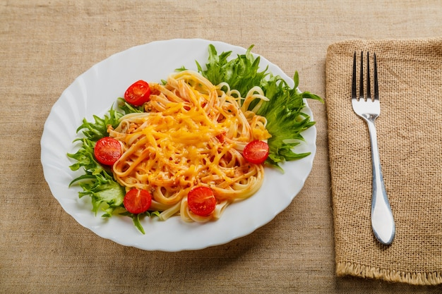 A plate of pasta with cheese and tomatoes decorated with herbs on a wooden table next to a linen napkin and a fork. horizontal photo