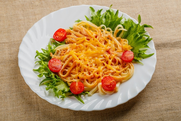 A plate of pasta with cherry tomatoes and cheese on a linen tablecloth.