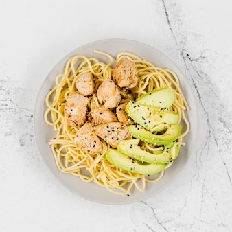 Plate of pasta with meat and avocado