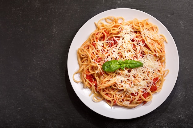 Plate of pasta with tomato sauce and parmesan on dark background, top view