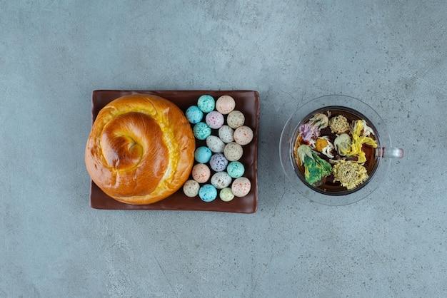 Piatto di pasticceria e caramelle con tazza di tè su marmo.