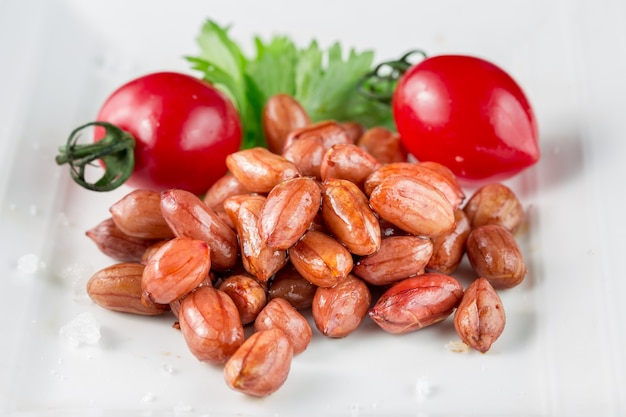 Plate of peanuts with tomatoes
